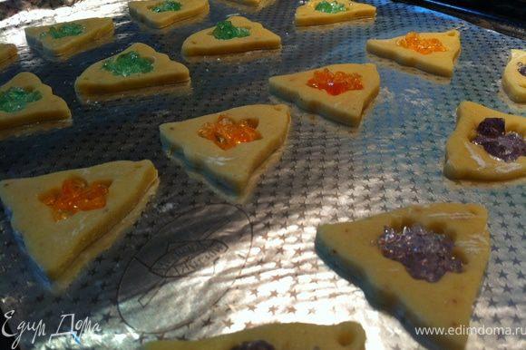 Внутрь каждой печенюшки чайной ложкой насыпать измельченные конфеты. Я клала с небольшой горкой. По желанию можно трубочкой для коктейля сделать дырочку для подвешивания. Я делаю шпажкой после выпекания- пока печенья горячие- протыкаются легко:)
