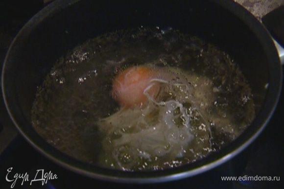 Вскипятить 500 мл воды, влить 1 ст. ложку уксуса, убавить огонь до минимума. Яйцо разбить, вылить в слабо кипящую воду с уксусом и варить 1–2 минуты.