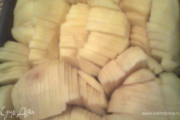 Поручаем кому-нибудь из домашних почистить картофель...Нарезаем картофелину очень тонко(чем тоньше,тем вкуснее!),стараясь сохранить её целостность.Если крупные,как у меня,режем вдоль,а потом каждую половину шинкуем,как капусту)Плотно укладываем в смазанную форму.Моя форма 17 на 25см.