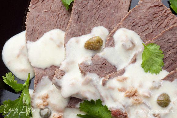 Выложить мясо в один слой на блюдо, полить сверху соусом и присыпать зеленью кинзы.