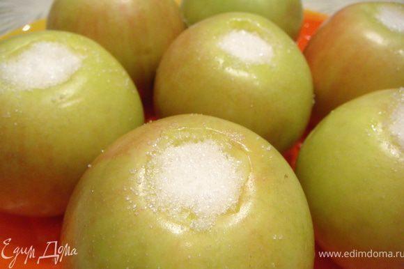 Яблоки вымыть, удалить сердцевину, не прорезая их насквозь. Засыпать внутрь каждого яблока по 1 ст.л. сахара. Отложить на 10 мин.