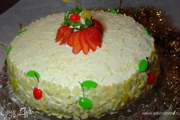Украшаем вишнями, клубникой и миндальными хлопьями, сверху посыпаем тертым белым шоколадом. Вы можете украсить торт по своему усмотрению.