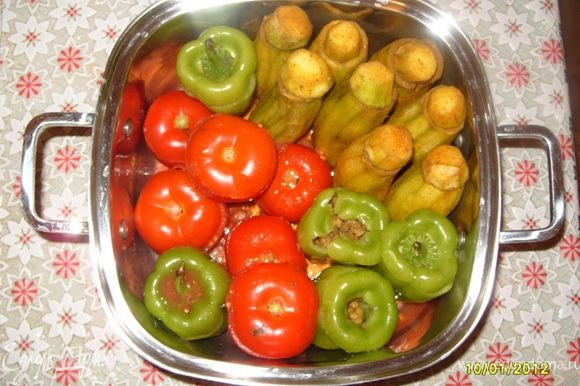 """Заполнить внутрь баклажан,помидоров и перцов жареным мясом с луком и горохом,положить сверху """"шапочки"""",уложить донышком вниз в кастрюлю."""