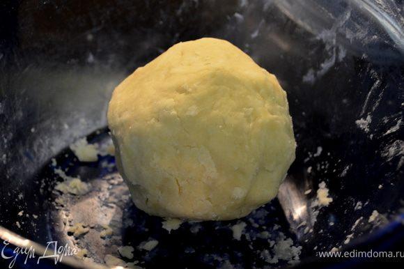 Сбрызнуть смесь 2 стол.ложками воды,перемешать вилкой.Скатать из теста шар,разделить пополам.