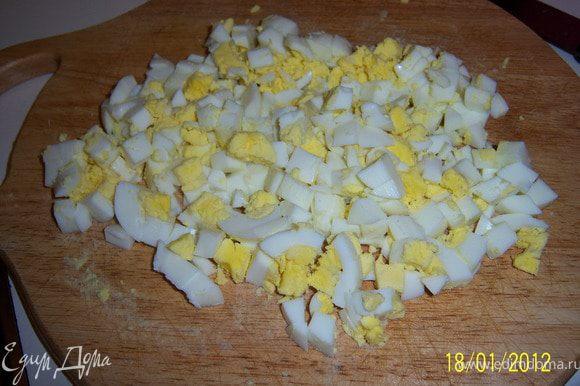 ...яйца сварить вкрутую, очистить от скорлупы и тоже нарезать кубиками.