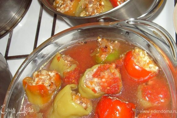 Фарширую перчик и укладываю в посуду для варки. У меня 2 варианта, так как мой муж не любит томатный соус - ему готовлю отдельно - просто заливаю кипяченной подсоленной водой, бросаю туда лаврушку и перец горошек. А вторую порцию заливаю смешанными в отдельной посуде протертые томаты, соль, сахар и кипяченную воду ~ 0,5л. Если воды будет мало, добавляем уже непосредственно в кастрюлю. Туда же отправляем пару листиков лаврушки и перец горошком.
