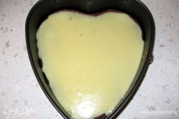 Разместить на дне разъёмной формы первый вырезанный корж. Сверху распределить половину крема.