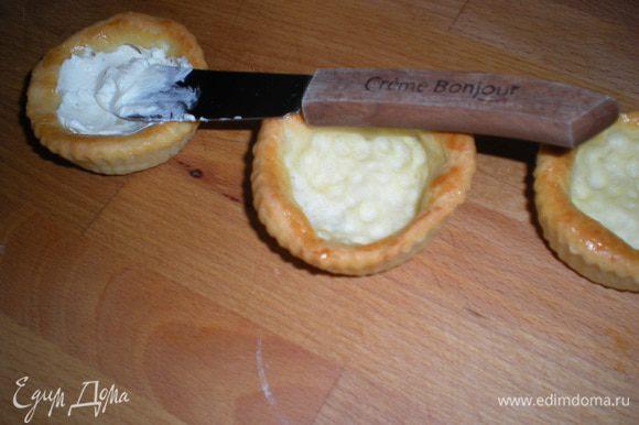 В тарталетки положить по чайной ложке творожного сыра.