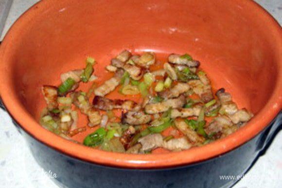 Приготовить глиняный горшочек. Его лучше замочить в воде за час до использования.Выложить на дно половину грудинки с луком.