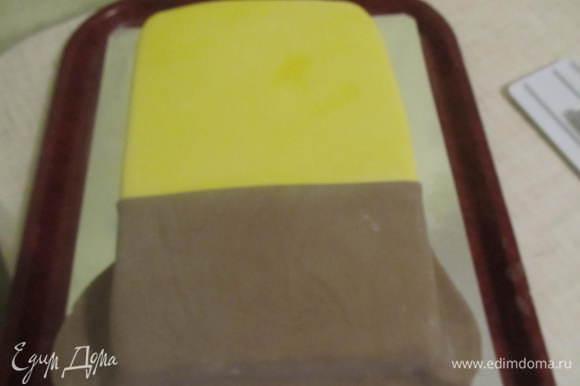 После того как тортик хорошо выровняли можно приступать и к украшению. Раскатать желтую мастику и накрыть им половину тортика (желательно больше половины). Вторую половину (поменьше) покрыть коричневой мастикой. Чтобы место стыка 2-х цветов было ровное, перед покрытием с одного края, надо отрезать ровненькую линию.