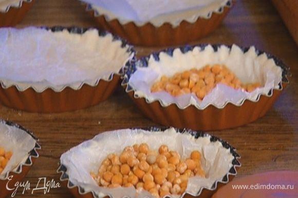Из бумаги для выпечки вырезать круги по количеству и размеру тарталеток, выложить бумагу на тесто и насыпать сверху горох.
