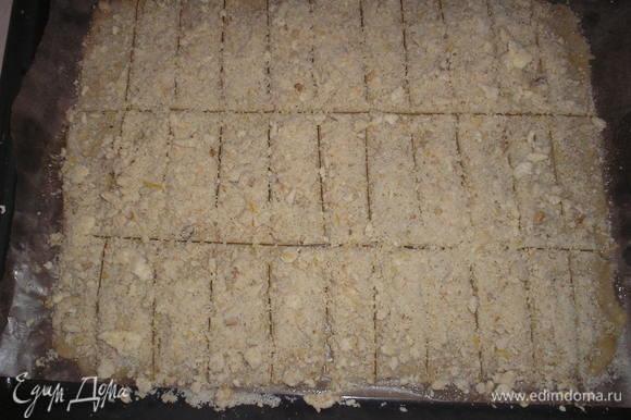 Смазать тесто слегка взбитым белком. Равномерно посыпать оставшимися крошками теста. Разрезать на полосы примерно 2х10см.