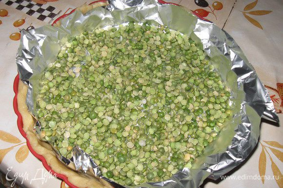 Уложить на тесто фольгу , а на фольгу насыпать 2 горсти сухого гороха.