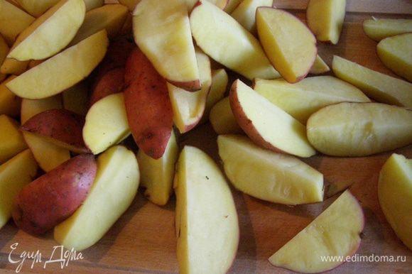Каждую картофелину разрежем на 4 части и обсушим с помощью полотенца