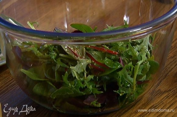 Листья салата посолить и поперчить, сбрызнуть оливковым маслом и разложить поверх салата.
