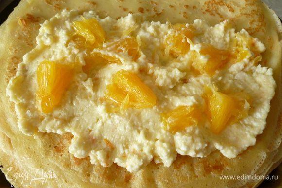 На половину блинчика выкладываем творожную массу,сверху кусочки апельсина.