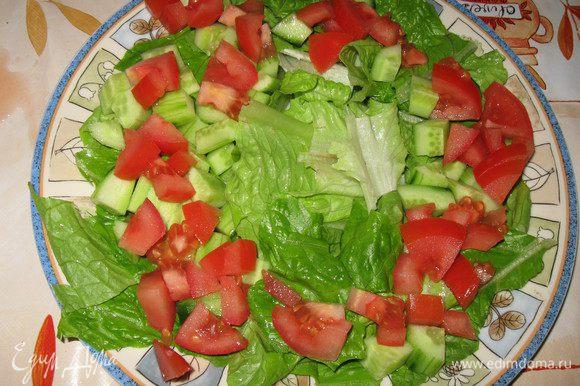 В тарелку порвать листья салата, сверху положить кубики огурца и помидора,посолить по вкусу.