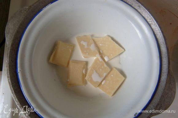 На водяной бане растопить белый шоколад в сливках, добавить сливочное масло. Остудить. Смазать получившимся кремом верхнюю часть пирога.