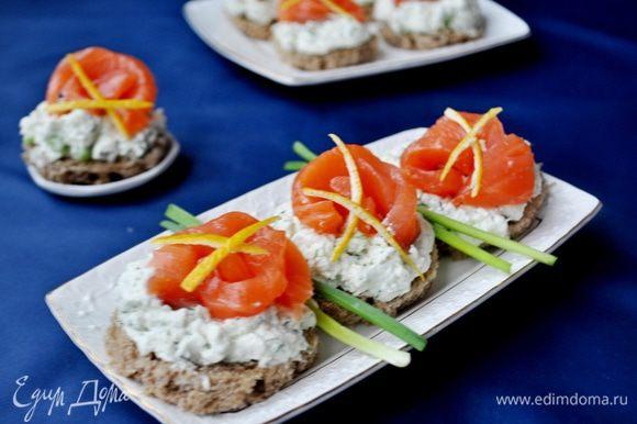 Рыбу нарезать на тонкие ломтики.На кружки хлеба выложить сырный крем,сверху ломтик рыбы,украсить лимонной цедрой,зелеью.Приятного аппетита!