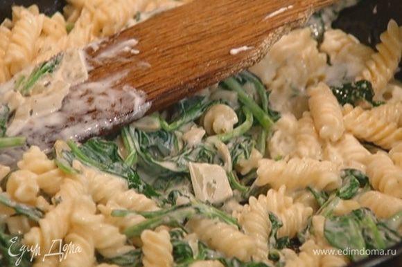 Отправить макароны в сковороду к шпинату с сыром, перемешать и прогревать 1–2 минуты на небольшом огне.