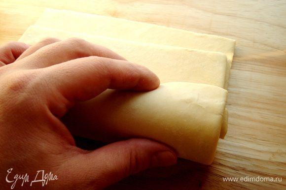 Листы слоёного теста сложить друг на друга,немного сдвинув к себе верхний слой.Свернуть тесто в рулет.Если слоёное тесто свёрнуто в рулон,то надо разморозить его не разворачивая.
