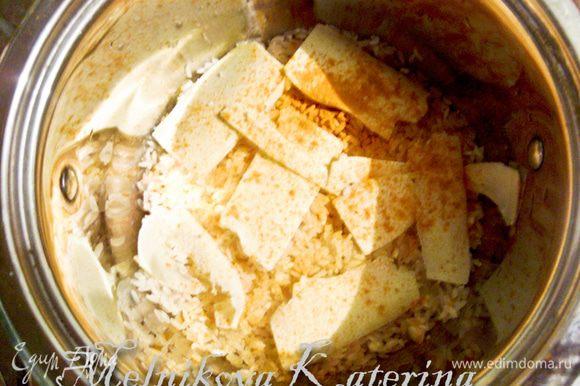 Рис промыть. Выложить в кастрюльку слоями, примерно по 1 см толщиной, перекладывая с тонкими ломтиками сливочного масла, пересыпая солью и куркумой. Залить рис водой в соотношении 1:2 и варить до готовности.