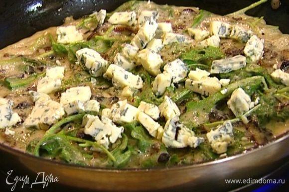 Дать омлету схватиться по краям, затем разложить сверху голубой сыр.