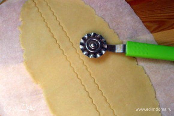 Снова раскатать срезанное тесто. Это удобно делать между двух листов пергамента. Колёсиком с зигзагом нарезать тесто на полоски. Взбить яйцо.