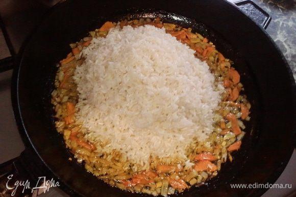 На разогретую тяжелую толстостенную сковороду налить растительное масло( я обычно часть специй и одну раздавленную дольку чеснока добавляю в это горячее масло еще до всего- чеснок вынимаю перед закладкой овощей), затем обжарить морковь и лук до золотистого цвета. В середину сковороды выложить рис и разровнять его таким образом, чтобы лук и морковь распределились по бортикам сковороды( это легко получается!)Следует учитывать, что блюдо увеличивается в объеме примерно на треть!