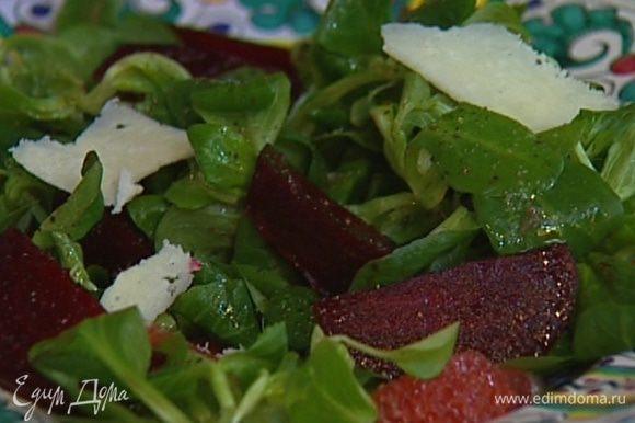 Сбрызнуть салат оливковым маслом, посолить, поперчить и посыпать нарезанным сыром.