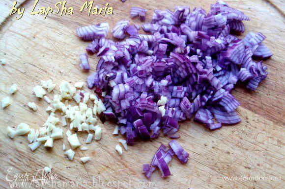 А пока приготовим соус. Для этого мелко нашинкуем лук и чеснок. И обжарим их на большом количестве оливкового масла до прозрачности лука.