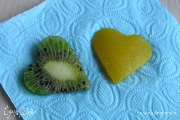 Аккуратно достать пирожные из колец, снять бумагу. Из кусочков киви и манго вырезать сердечки, обсушить на салфетке.