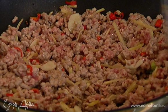 В сковороде-вок разогреть кунжутное и оливковое масло, выложить имбирь, чили, чеснок и свиной фарш и, непрерывно помешивая, обжарить.