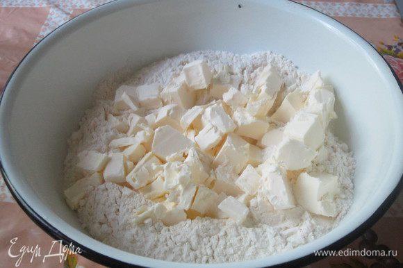Просеиваем муку. На неё выкладываем нарезанное кусочками сливочное масло (или маргарин).