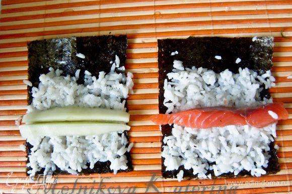 """Выложить на обе части нори по небольшой горсти риса. Разровнять, оставляя с одного края """"хвост"""" шириной примерно 2 см (ролл в дальнейшем будет держаться благодаря этому """"хвосту""""). На одну часть выложить огурец, но вторую часть - полоску лосося."""