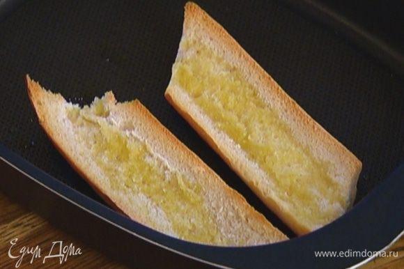 Выложить хлеб на противень срезами вверх, сбрызнуть оливковым маслом и обжаривать в разогретой духовке до появления золотистой корочки.