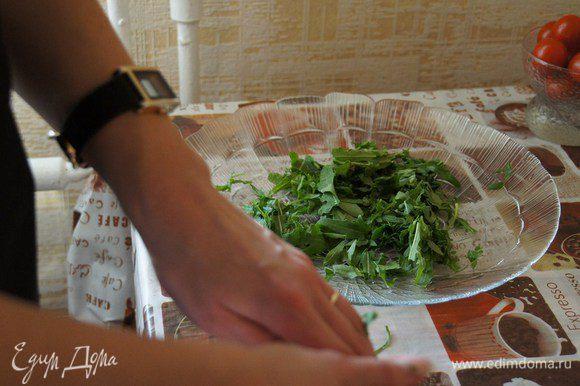 На большое плоское блюдо выкладываем рукколу, которую просто рвем руками, немного сбрызгиваем оливковым маслом и бальзамическим уксусом
