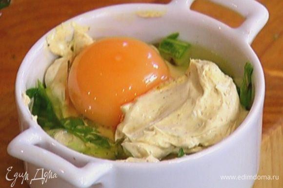 Влить в каждую форму по 1 ч. ложке сметанного соуса, равномерно распределить, а сверху разбить по яйцу так, чтобы желток не растекся. Добавить еще по 1 ч. ложке соуса, немного посолить.