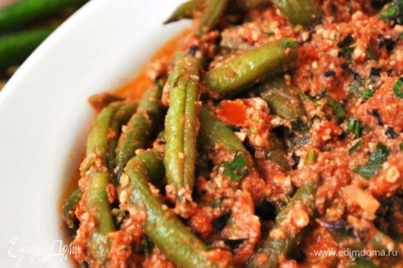 В сотейник положить лук, томаты, фасоль, ореховую заправку, зелень и тушить 10 минут.