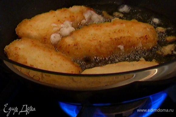 Разогреть в сковороде-вок оливковое масло и обжарить рыбные пальчики с двух сторон.