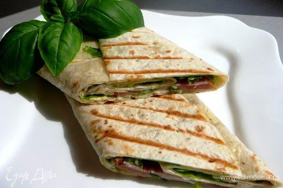 На смазанную соусом лепешку выложить салатные листья, ломтики ветчины и сыра и свернуть рулетом. Такос можно подавать сразу, а можно обжарить на сковороде-гриль...