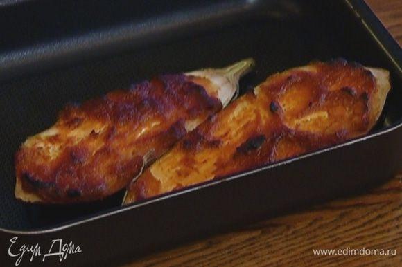 Баклажан вымыть и разрезать вдоль пополам, выложить на противень срезами вверх и смазать соевой заправкой. Отправить в разогретую духовку на 15 минут.
