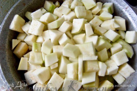 Пока тушатся овощи очистить кабачки от кожуры, нарезать на кубики. Добавить к овощам. Все перемешать и убавить огонь до минимума, накрыть крышкой и тушить 1 час, помешивая каждые 20 минут.