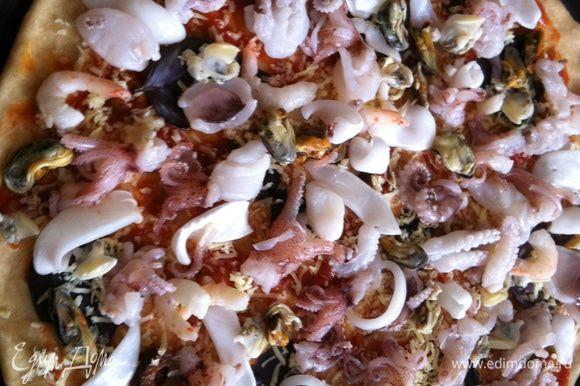 Выложить равномерно морепродукты. Поставить в предварительно разогретую до 200 градусов духовку минут на 20-25