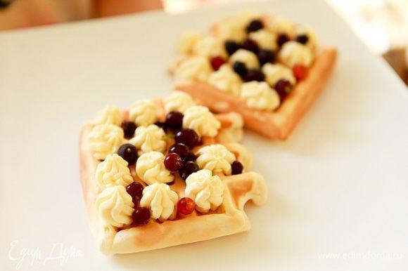 Взбить сливки с ванилином, сахаром. Из шприца выдавить сливки на вафли. Посыпать ягодами.