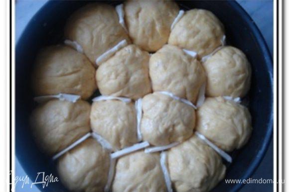 Разделить тесто на кусочки и скатать из них шарики. Выложить шарики в смазанную маслом форму для выпечки. Между шариками хорошо бы проложить кусочки сливочного масла, легче будут отделяться булочки друг от друга. Накруть пампушки полотенцем и поставить в теплое место на 20-25 минут.