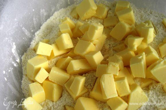 Охлажденный маргарин нарезать маленькими кубиками и смешать с мукой.