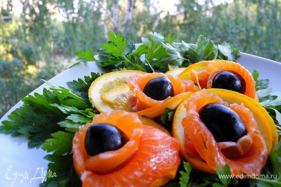 """Затем вынуть из холодильника, очистить от """"шубы"""", нарезать тонкими ломтиками. Если понравился вариант подачи, то этими ломтиками обернуть оливки и """"упаковать"""" в кулечки из кружочков апельсинов. На зелени, конечно, будет смотреться наряднее)))"""