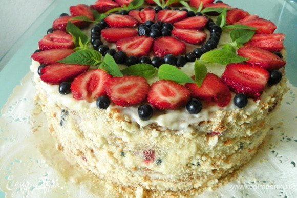 Оставшийся крем распределяем на верхний корж и на бока торта. Украшаем торт сверху ягодами, листиками мяты. Бока по желанию можно обсыпать крошками от коржей или оставить просто белыми.