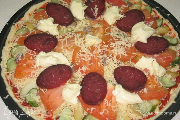 Посыпать сверху сыром (1/2 часть оставшегося количества). Помидор нарезать тонкими пластинками и разложить сверху. также поступить и с колбасой. В промежутки между кусочками колбасы выложить чайной ложкой плавленный сыр